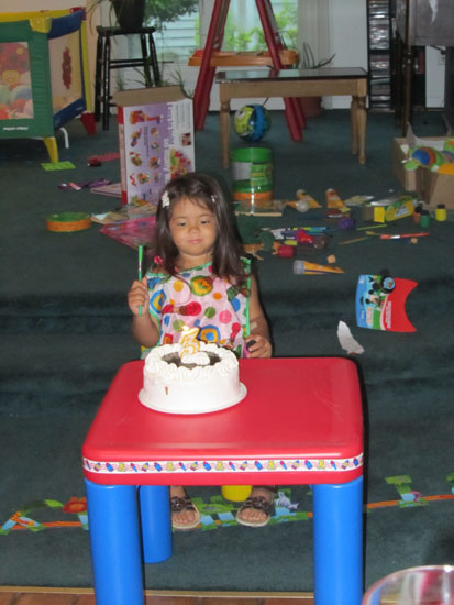 In her painting smock with her cake