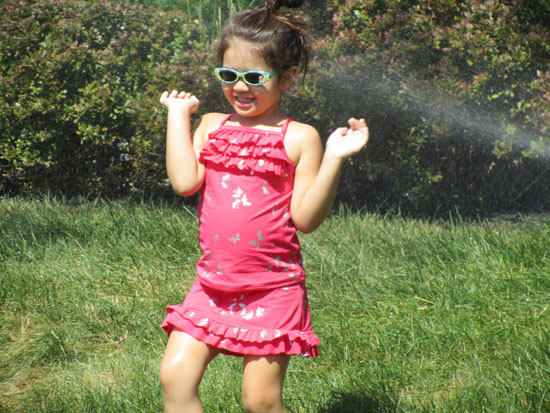Playing in the sprinkler in the front yard