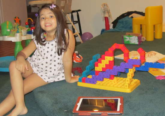 Posing with her building block sculpture of an elephant in an artsy zoo enclosure