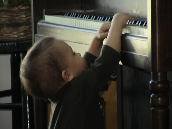 Standing up and reaching the piano on his own