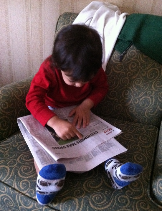 Reading the newspaper. Seriously. He's picking out words and reading them aloud