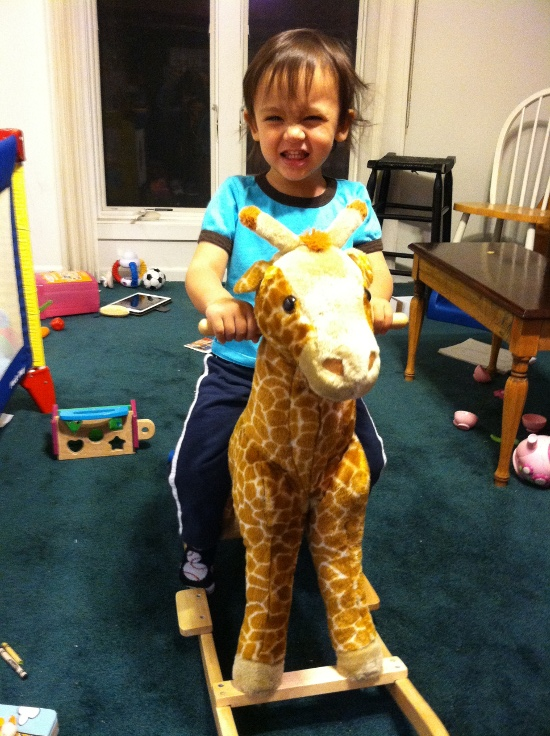 Birthday boy happily riding Rocky the Rocking Giraffe
