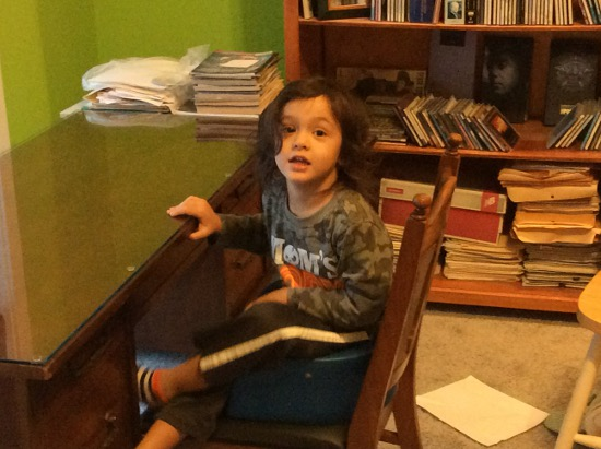 Adik sits at Granny Jean's desk on the blue bouncy chair
