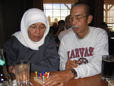 Mak and Abah playing the peg game